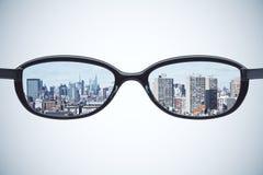 Klart visionbegrepp med glasögon med megapolisstaden på whit Arkivbilder