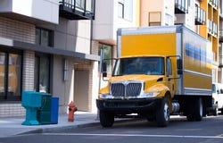Klasa średnia koloru żółtego semi ciężarówka z pudełkowatą przyczepą na miasto ulicie f obraz stock