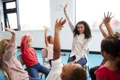 Klasa dziecięcy dzieci w wieku szkolnym siedzi na krzesłach w okręgu w sali lekcyjnej, podnosi ręki z ich żeńskim nauczycielem, z obrazy stock