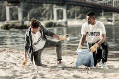 Klasgenoten die aan elkaar spreken terwijl het verzamelen van lege koffiekoppen op het strand royalty-vrije stock foto