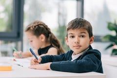 Klasgenoten die bij bureau zitten en in oefenboeken schrijven royalty-vrije stock fotografie