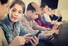 Klasgenoten die hun smartphones gebruiken intensief tijdens klassen royalty-vrije stock foto's