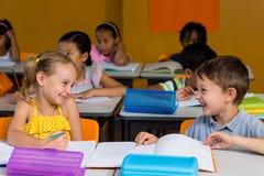 Klasgenoten die in klaslokaal lachen royalty-vrije stock afbeeldingen