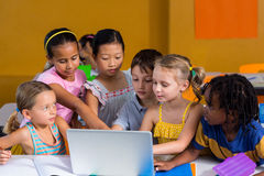 Klasgenoten die laptop met behulp van stock foto