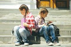 Klasgenoten die met schooltassen zitten stock afbeelding