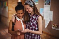 Klasgenoten die mobiele telefoon in gang met behulp van op school stock afbeelding