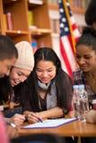 Klasgenoten die pret hebben en voor lezing bestuderen Stock Afbeelding