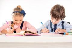 Klasgenoten die thuiswerk in notitieboekjes schrijven royalty-vrije stock foto's