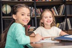 Klasgenoten die thuiswerk samen in bibliotheek doen stock fotografie