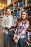 Klasgenoten die zich in bibliotheek het glimlachen bij camera bevinden stock afbeelding