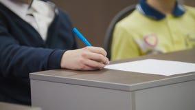 Klasgenoten op school tijdens de les - kinderen die lijst situeren en pennen houden stock fotografie