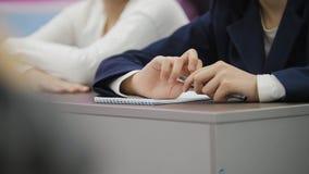Klasgenoten op school tijdens de les - kinderenmeisjes die lijst situeren en pennen houden stock afbeelding