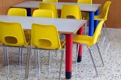Klaslokaal met gele stoelen in de kleuterschool stock afbeeldingen