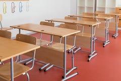 Klaslokaal met houten bureaus en stoelen stock foto