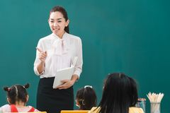 In klaslokaal, onderwijst de Aziatische leraar student stock afbeeldingen