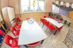 Klaslokaalkinderdagverblijf met rode stoelen en bureaus voor kinderen royalty-vrije stock afbeeldingen