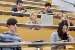 Klasse, die in einem Vorlesungssal hört Lizenzfreies Stockbild