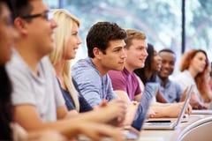 Klasse von den Hochschulstudenten, die Laptops im Vortrag verwenden stockfotos