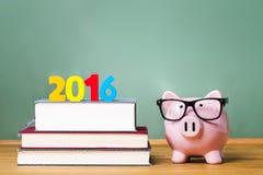 Klasse von Thema 2016 mit Lehrbüchern und Sparschwein mit Gläsern Lizenzfreies Stockfoto