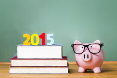Klasse von Thema 2015 mit Lehrbüchern und Sparschwein mit Gläsern Lizenzfreie Stockfotos