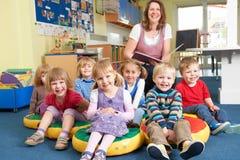 Klasse von Vorschule-Kindern zur Geschichten-Zeit mit Lehrer Lizenzfreie Stockbilder