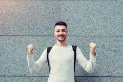 Klassen annulliert Glücklicher arabischer Student draußen Erfolgreiche und überzeugte angehobene Hände des jungen Mannes lizenzfreie stockbilder