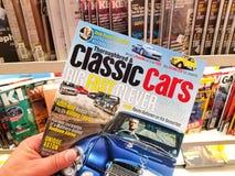 klassiek auto'stijdschrift in een hand stock afbeeldingen