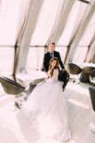 Klassiek familieportret van bruidzitting op stoel en bruidegom die zich achter haar bij restaurant bevinden Royalty-vrije Stock Fotografie