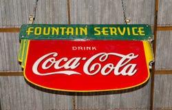 Klassiek handelsmerk brandmerkend embleem van Coca-Cola op rood metaalblad met het groene de Dienst ` van de tekst` Fontein hange royalty-vrije stock afbeelding