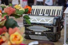 Klassiek muzikaal instrument een harmonika in zwarte kleur, met bloemen op het stadium stock afbeeldingen