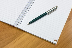 Klassiek pen en notitieboekje op houten bureau Stock Afbeelding