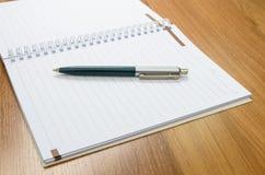 Klassiek pen en notitieboekje op houten bureau Stock Foto's