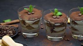 Klassiek tiramisudessert in een glas en savoiardikoekjes op steen dienende raad stock videobeelden