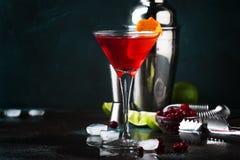 Klassieke alcoholische cocktail kosmopolitisch met wodka, likeur, Amerikaanse veenbessap, kalk, ijs en oranje schil, donkere bart stock afbeelding