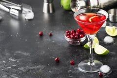 Klassieke alcoholische cocktail kosmopolitisch met wodka, likeur, Amerikaanse veenbessap, kalk, ijs en oranje schil, grijze barte stock afbeeldingen