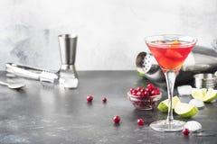 Klassieke alcoholische cocktail kosmopolitisch met wodka, likeur, Amerikaanse veenbessap, kalk, ijs en oranje schil, grijze barte stock foto's