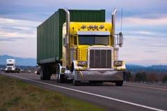 Klassieke Amerikaanse krachtige gele semi vrachtwagen met chroomzuigbuis Stock Foto