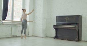 Klassieke balletdanser die releve bij staaf uitoefenen stock videobeelden