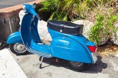 Klassieke blauwe Vespa-Sprint 150 geparkeerde autopedtribunes Stock Foto's