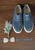 Klassieke bruidegomtoebehoren: houten vlinderdas en blauwe schoenen op een houten lijst Stock Foto's