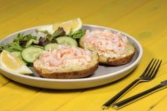 Klassieke gezonde vermageringsdieetmaaltijd Garnaal op jasjeaardappel met salade stock foto