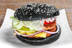 Klassieke hamburger met zwart brood en verse groenten op een witte plaat stock afbeelding