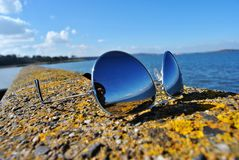 Klassieke hoogste de spiegelzonnebril van het kanonontwerp op het traliewerk, zilver met donkere bezinning Stock Fotografie