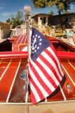 Klassieke houten snelheidsboot met zeevaartdievlag voor een huis op het meer wordt gedokt - bekijk van terug met vlag in nadruk royalty-vrije stock foto's