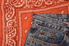 Klassieke jeans met vijf zakkenclose-up Paisley vormde bandana, klassieke rode en witte halsdoek, fietser hoofdsjaal ruw royalty-vrije stock foto's