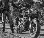 Klassieke motorfiets en fietser op de rand van de weg in zwarte royalty-vrije stock foto's
