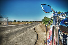 Klassieke motorfiets op de rand van een windende weg stock foto