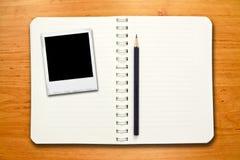 Klassieke onmiddellijke fotoframes op notitieboekje Stock Fotografie