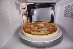 Klassieke Pizzaclose-up in microgolf Half afgewerkt die product in te verwarmen oven wordt geplaatst stock afbeelding