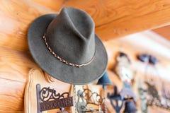 Klassieke uitstekende vilten die hoed op muur wordt gehangen Ingang van rustiek blokhuis Welkom plaat dichtbij deur Landelijke le royalty-vrije stock afbeelding